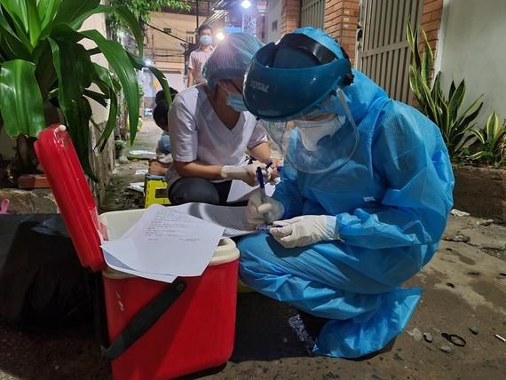 Nhân viên y tế chuẩn bị lấy mẫu xét nghiệm cho người dân