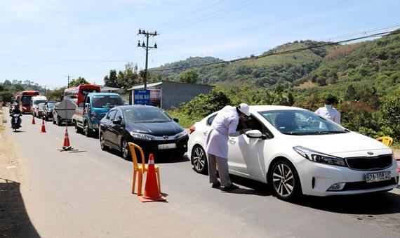 Nhân viên y tế kiểm dịch ở cửa ngõ trên quốc lộ 20 từ TP HCM về Đà Lạt đầu năm 2021. Ảnh: Khánh Phúc