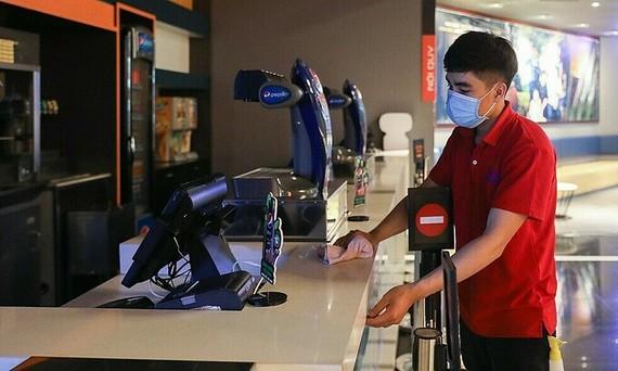 Nhân viên một rạp chiếu phim ở quận 1 dọn dẹp sau khi TPHCM dừng dịch vụ không thiết yếu để chống dịch hôm 9-2. Ảnh: Quỳnh Trần.