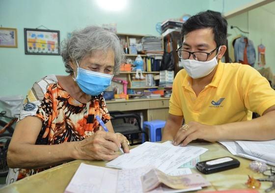 Nhân viên Bưu điện TPHCM tới tận nhà chi trả lương hưu, trợ cấp bảo hiểm xã hội tới người dân trên địa bàn TPHCM. Ảnh: VIỆT DŨNG