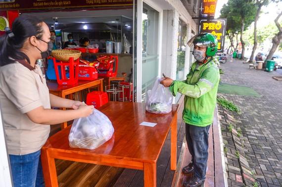 Shipper nhận hàng tại quán phở trên đường Bùi Bằng Đoàn, quận 7, TP.HCM, để đi giao cho khách. Ảnh: Quang Định.