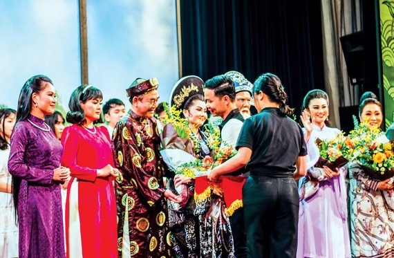 """SCB representative presented flowers to artists participating in the program """"Cai Luong-Hundred Years of Origin""""."""