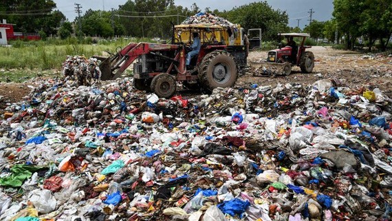 Workers load garbage into a dump truck at a trash dump teeming with plastic bags in Islamabad.    © AFP/Jiji