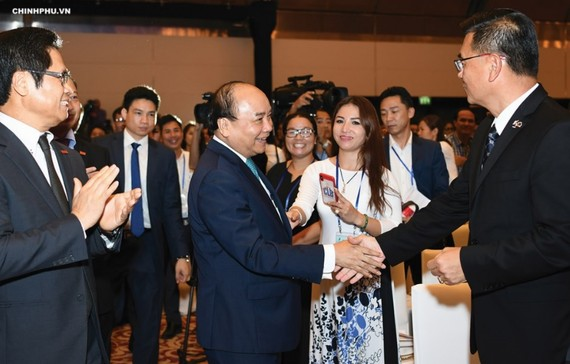 Prime Minister Nguyen Xuan Phuc talks with delegates attending the Conference in 2018.