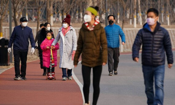People wearing masks walk at a park in Beijing on Feb. 29, 2020. (Lintao Zhang/Getty Images)
