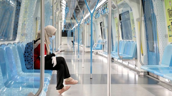 A woman wearing protective mask and gloves seen on a Mass Rapid Transit train during a movement control order in Kuala Lumpur on Sunday.   © Reuters