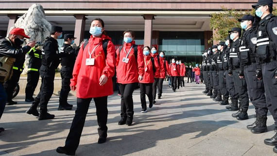 Policemen salute medical workers from Mongolia in Wuhan, Hubei Province on March 18. The workers had been brought to the province to help contain the coronavirus outbreak.   © AP