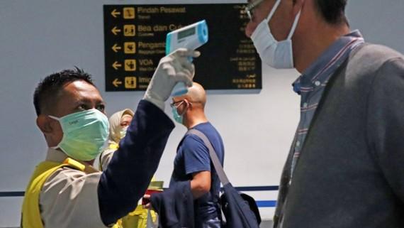 A health officer checks the temperature of an arriving passenger at Jakarta's Soekarno-Hatta International Airport. (Photo by Ken Kobayashi)