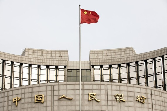 A Chinese flag flies in front of the People's Bank of China headquarters in Beijing, China, on Monday, Jan. 7, 2019. The central bank on Friday announced another cut to the amount of cash lenders must hold as reserves in a move to release a net 800 billio