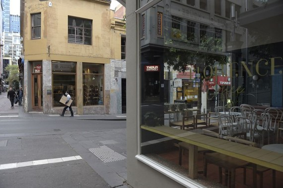 Chairs sit stacked on tables in a closed cafe during coronavirus lockdown in Melbourne on March 23. Photographer: Carla Gottgens/Bloomberg