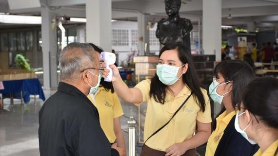 Người dân được đo thân nhiệt tại Thái Lan - Ảnh: THE THAIGER