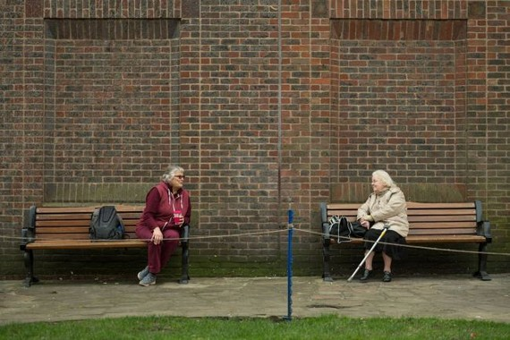 Two women keep 6 feet (1.8 meters) apart as they speak to each other from adjacent park benches amidst the novel coronavirus COVID-19 pandemic, in the centre of York, northern England on March 19, 2020. (Image: © OLI SCARFF/AFP via Getty Images)