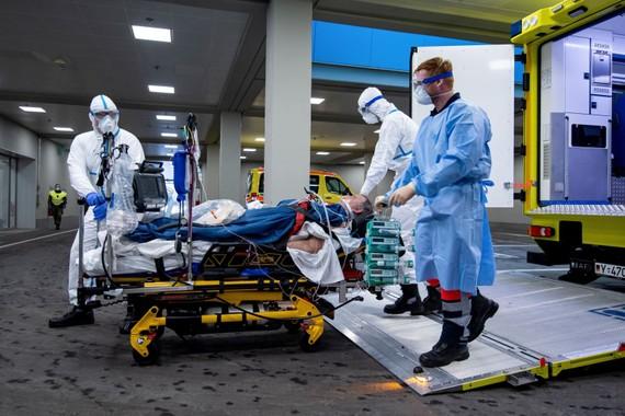 Nhân viên y tế chuyển bệnh nhân nhiễm COVID-19 lên xe cứu thương tới bệnh viện ở Ulm, tây nam nước Đức, ngày 29/3. Ảnh: AFP/TTXVN