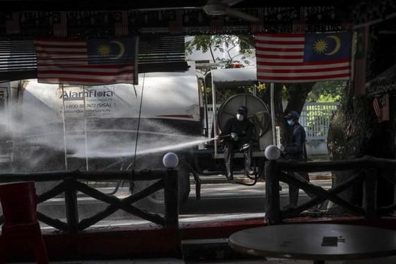 Nhân viên y tế tẩy trang khu vực quanh nhà thờ Sri Petaling. Ảnh: Straits Times.