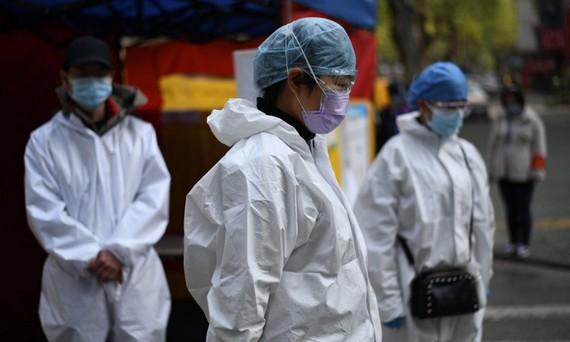 Tình nguyện viên Trung Quốc mặc niệm nạn nhân Covid-19 hôm 4/4. Ảnh: AFP.