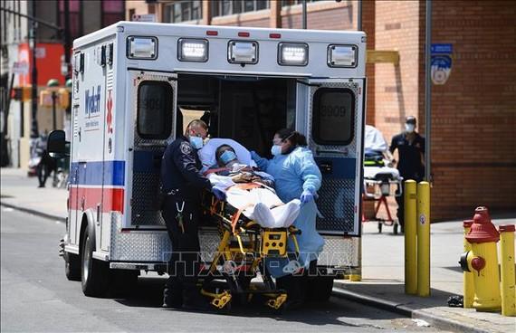 Nhân viên y tế chuyển nạn nhân nhiễm COVID-19 tới bệnh viện ở Brooklyn, New York, Mỹ, ngày 7/4. Ảnh: AFP/TTXVN