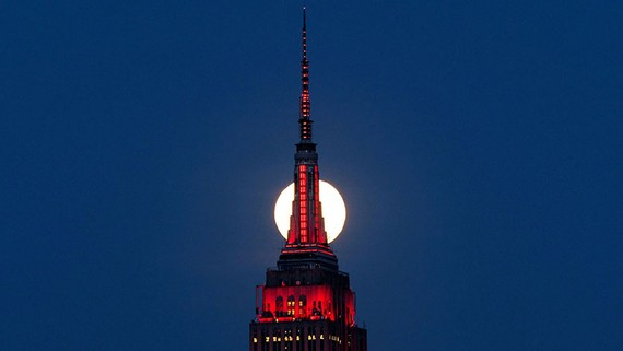 A supermoon rises behind the Empire State Building, glowing red in solidarity with coronavirus victims.   © Reuters