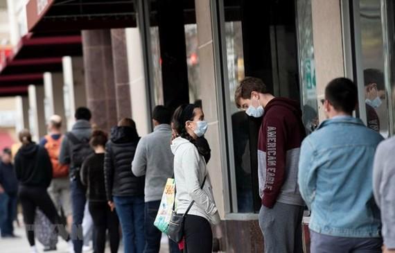 Người dân xếp hàng bên ngoài siêu thị tại Arlington, Virginia, Mỹ ngày 4/4 vừa qua trong bối cảnh dịch COVID-19 lan rộng. (Ảnh: THX/TTXVN)