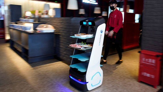 A robot delivers food to diners at a restaurant, following an outbreak of the novel coronavirus disease, in Shanghai.   © Reuters