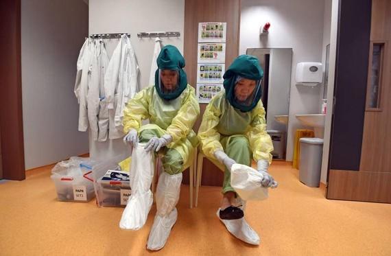 Nhân viên y tế trang bị đồ bảo hộ khi chữa trị cho bệnh nhân mắc COVID-19 tại Singapore. Ảnh: ST