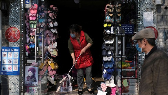 A woman wearing a face mask cleans the entrance of a shop in Beijing on April 17. The coronavirus outbreak has hit China's domestic demand hard.   © Reuters