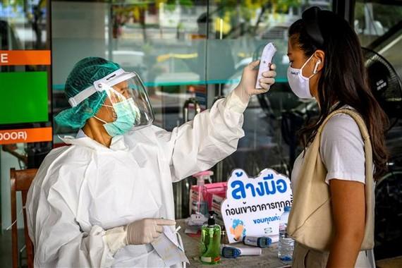 Nhân viên y tế kiểm tra thân nhiệt phòng lây nhiễm COVID-19 tại Bangkok,Thái Lan, ngày 24/4/2020. Ảnh: AFP/TTXVN
