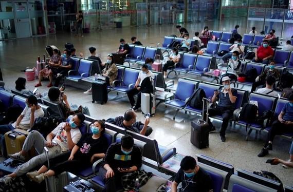 Các hành khách chờ tàu ở nhà ga Vũ Hán, Trung Quốc đều đeo khẩu trang (Ảnh Reuters)