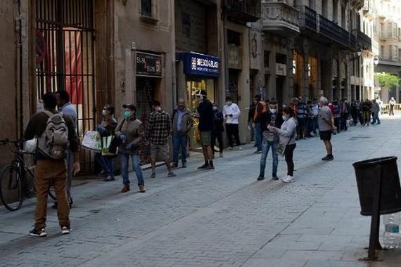 Người dân xếp hàng khi các tình nguyện viên phân phát thực phẩm tại nhà thờ Santa Anna ở Barcelona vào ngày 15/5/2020. (Nguồn: AFP)