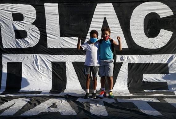 Hai cậu bé da màu đứng trước khẩu hiệu của người biểu tình căng ngoài công viên Lafayette ngày 7/6Ảnh: AP