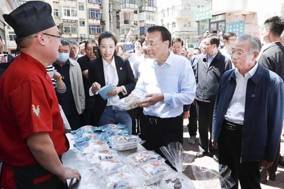 Thủ tướng Lý Khắc Cường ghé thăm một quầy bán hàng rong. (Ảnh: THX)