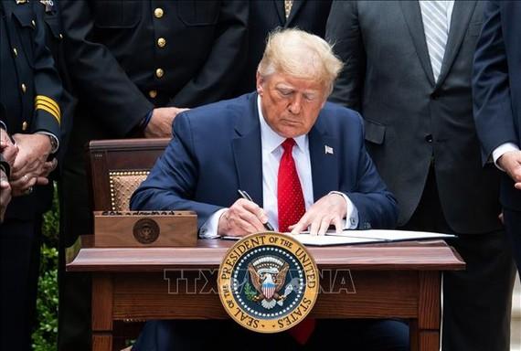 Tổng thống Mỹ Donald Trump ký sắc lệnh cải tổ cảnh sát tại Washington DC., ngày 16/6/2020. Ảnh: AFP/TTXVN