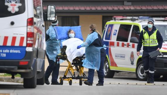 Nhân viên y tế chuyển bệnh nhân nghi mắc COVID-19 lên xe cứu thương tại bang Victoria, Australia ngày 27/7/2020. Ảnh: AFP/TTXVN