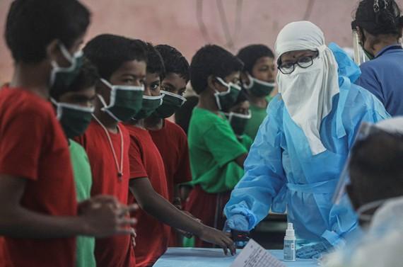 Nhân viên y tế kiểm tra sức khỏe những đứa trẻ ở trại trẻ tại Mumbai, Ấn Độ ngày 28-7-2020 - Ảnh: REUTERS
