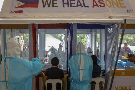 Nhân viên y tế xét nghiệm cho nhân viên chính phủ ở TP Quezon, Đông Bắc Manila hôm 30-7. Ảnh: EPA