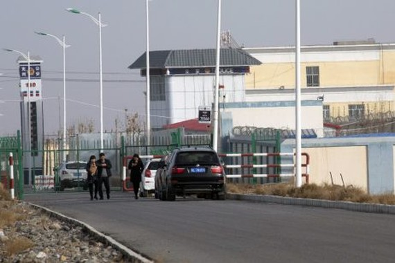 In this December 3, 2018, file photo, people walk by a police station by the front gate of the Artux City Vocational Skills Education Training Service Center in Artux in western China's Xinjiang region.  Credit: AP Photo/Ng Han Guan, File