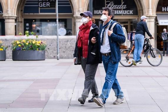 Người dân đeo khẩu trang phòng dịch COVID-19 khi di chuyển trên phố ở Munich, Đức. Ảnh: THX/TTXVN