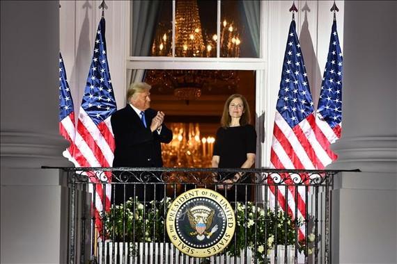 Tổng thống Mỹ Donald Trump (trái) chúc mừng bà Amy Coney Barrett (phải) sau lễ tuyên thệ nhậm chức Thẩm phán Tòa án Tối cao tại Washington, DC ngày 26/10/2020. Ảnh: AFP/TTXVN
