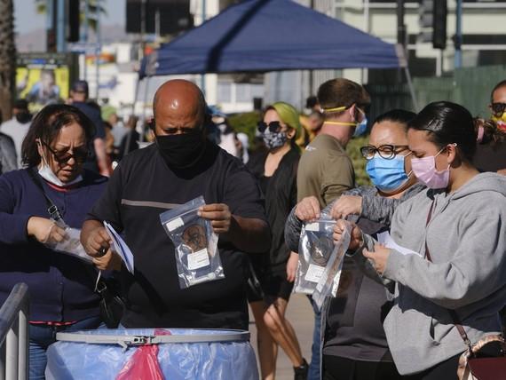 Mọi người thả bộ xét nghiệm của họ vào một thùng chứa tại một địa điểm thử nghiệm coronavirus ở khu vực Bắc Hollywood của Los Angeles vào thứ Bảy 5/12/2020. Ảnh: Richard Vogel/AP