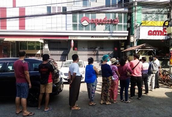 Người dân xếp hàng trước một chi nhánh ngân hàng ở Yangon để chờ rút tiền. Ảnh: Reuters.