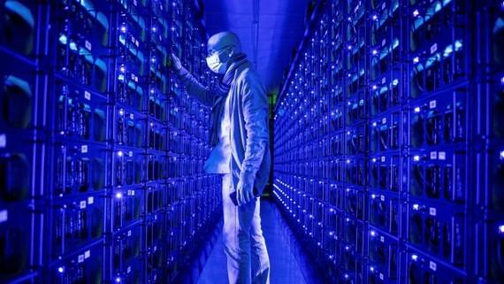 Một nhân viên đeo khẩu trang bảo vệ kiểm tra các hệ thống đào tiền điện tử Ethereum và Zilliqa tại trang trại tiền điện tử Evobits ở Cluj-Napoca, Romania © Bloomberg