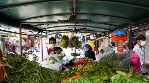 Người dân mua rau từ một xe bán dạo khi nhiều chợ tươi sống đóng cửa 14 ngày, ở Phnom Penh, Campuchia, ngày 17/4/2021. Photo: Cindy Liu / Reuters