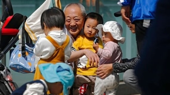 An elderly man plays with children near a commercial office building in Beijing on May 10, 2021. (AP)