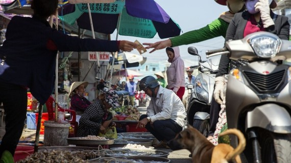 A vendor hands money to a motorist as people buy seafood at the Duong Dong market in Phu Quoc, Vietnam. Photographer: Maika Elan/Bloomberg , Bloomberg