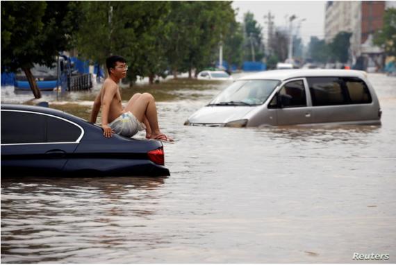 Một người đàn ông ngồi trên một chiếc xe bị mắc kẹt trên con đường ngập nước sau trận mưa lớn ở Trịnh Châu, tỉnh Hà Nam, Trung Quốc, ngày 22 tháng 7 năm 2021.