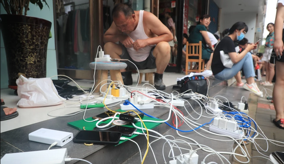 Mọi người sạc điện thoại di động bên ngoài một cửa hàng ở Trịnh Châu có điện. Ảnh: Getty Images