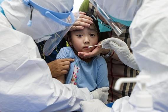Một đứa trẻ phản ứng với miếng gạc ngoáy họng trong quy trình xét nghiệm hàng loạt tại Vũ Hán, Trung Quốc. Nguồn ảnh:  APNews.
