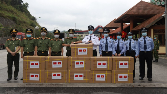 Representatives of China and Vietnam pose for a group photo with COVID-19 prevention and control materials at a border crossing between China and Vietnam, on May 12, 2020. /Chinese Embassy in Vietnam