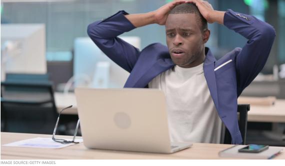 Một người đang lo lắng nhìn chằm chằm vào màn hình máy tính của mình một cách kinh ngạc. @Getty Images
