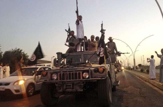 Các chiến binh IS diễu hành trên một chiếc xe bọc thép do lực lượng an ninh Iraq điều động vào năm 2014. Ảnh: AP