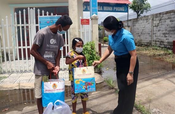 Representative of the Kiên Giang Labour Federation give food to poor residents in Bình An Commune, Châu Thành District. — VNA/VNS Photo Lê Huy Hải